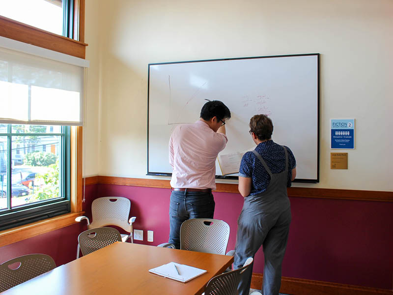 Two people at whiteboard in study room